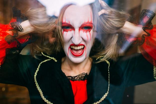 La donna pazza in costume della strega posa dietro il vetro