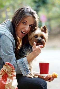 La donna pranza mentre passeggia con il suo cane