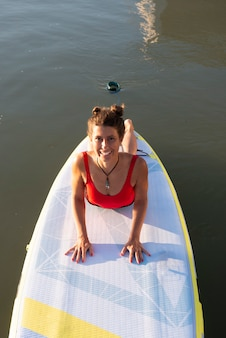 La donna pratica la posa del cane con la testa in giù durante la sua pratica yoga su una tavola da paddle