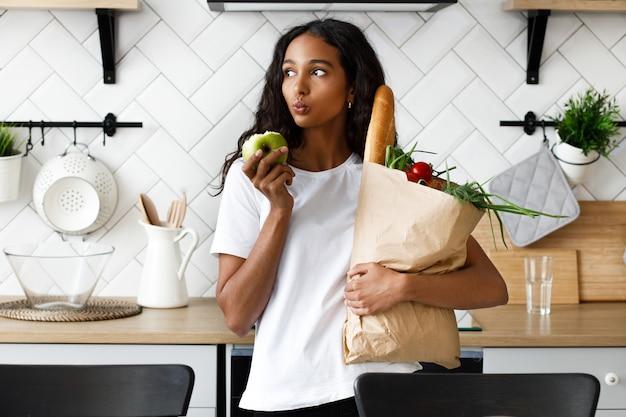 La donna premurosa del mulatto sta tenendo il pacchetto pieno con verdure fresche in una mano e mela morsicata nell'altra, sulla moderna cucina bianca