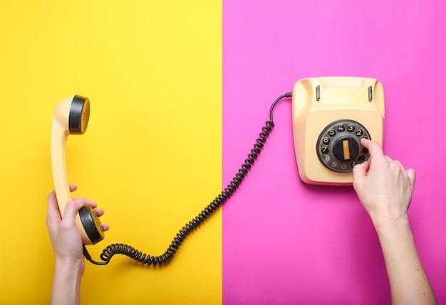 La donna prende il numero del telefono rotativo e tiene il microtelefono su uno sfondo di carta colorata. vista dall'alto, minimalismo