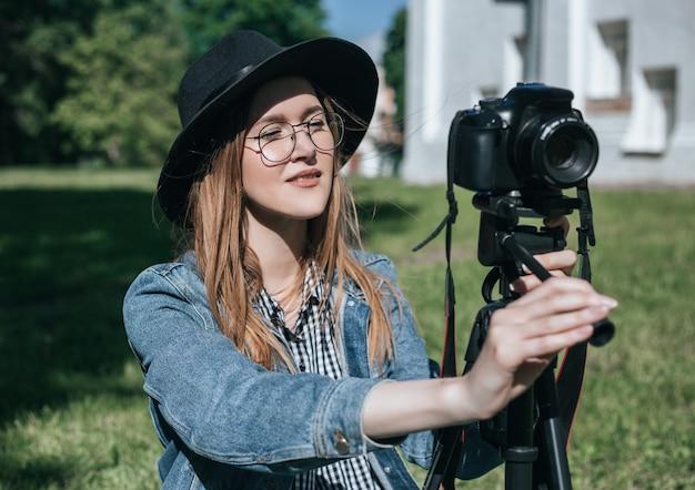La donna prende la foto con la macchina fotografica professionale sul treppiede nel parco dell'estate