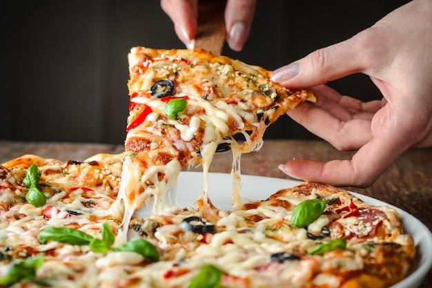 La donna prende un pezzo di pizza