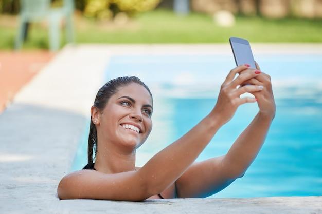 La donna prende un selfie alla piscina