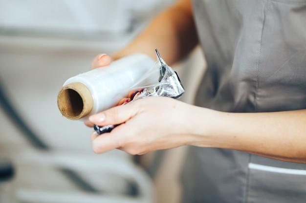 La donna prepara gli strumenti per il trucco permanente per il lavoro usa il nastro avvolgente per la sterilità