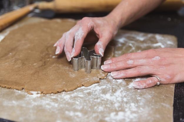 La donna produce i biscotti del pan di zenzero di natale su nero e su rosso