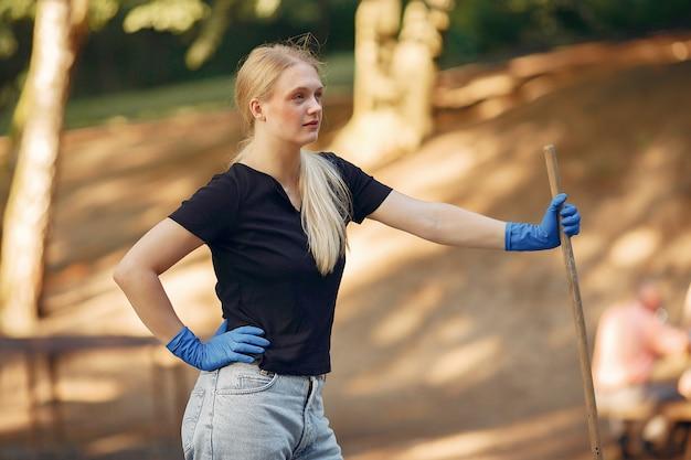 La donna raccoglie le foglie e pulisce il parco