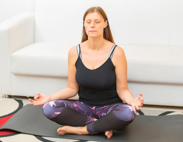 La donna rilassata sta facendo la figura di yoga del loto a casa