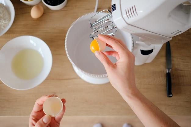 La donna rompe le uova di pollo in una ciotola nella cucina.
