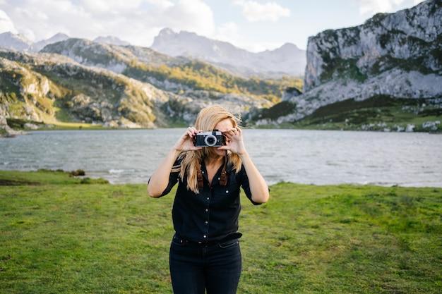 La donna scatta foto in un paesaggio montano
