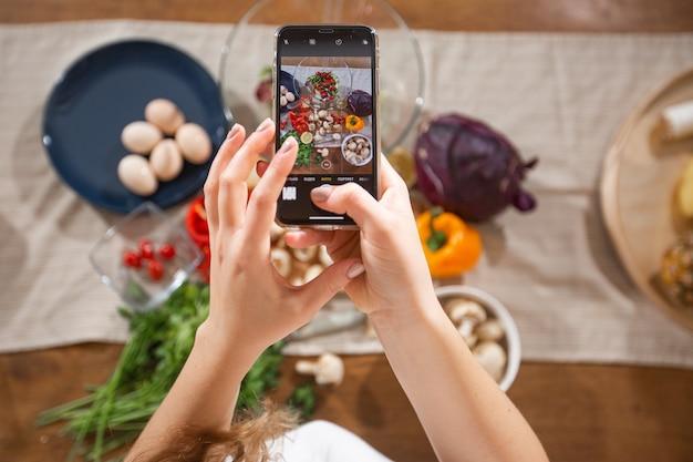 La donna scatta una foto di diverse belle verdure e verdure con un telefono cellulare nella sua cucina. fotografia di cibo per smartphone. alimentazione sana, cibo vegetariano, dieta. per perdita di peso e disintossicazione.