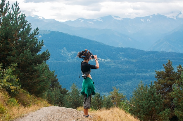 La donna scatta una foto di montagne