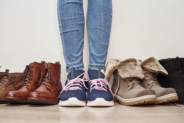 La donna sceglie comode scarpe in pelle marrone tra un mucchio di paia diverse
