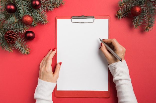 La donna scrive obiettivi, lista di controllo, piani e sogni per il nuovo anno. lista dei desideri per natale. vista dall'alto