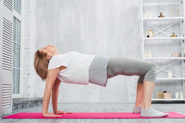 La donna senior che fa l'allungamento si esercita sopra la stuoia rosa a casa