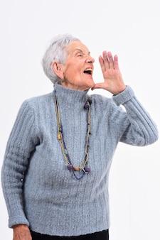 La donna senior che mette una mano in bocca e sta gridando su fondo bianco