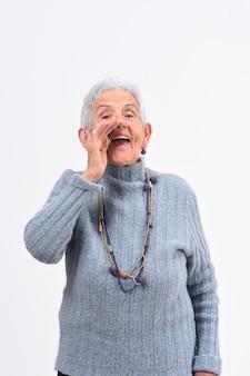 La donna senior che mette una mano in labo e sta gridando su fondo bianco