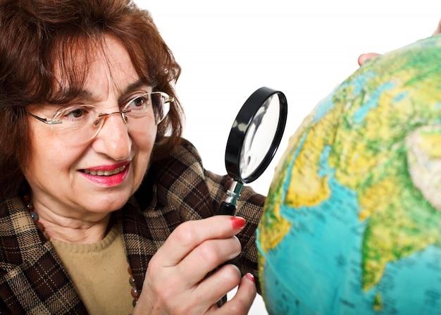 La donna senior con la lente d'ingrandimento esamina il globo