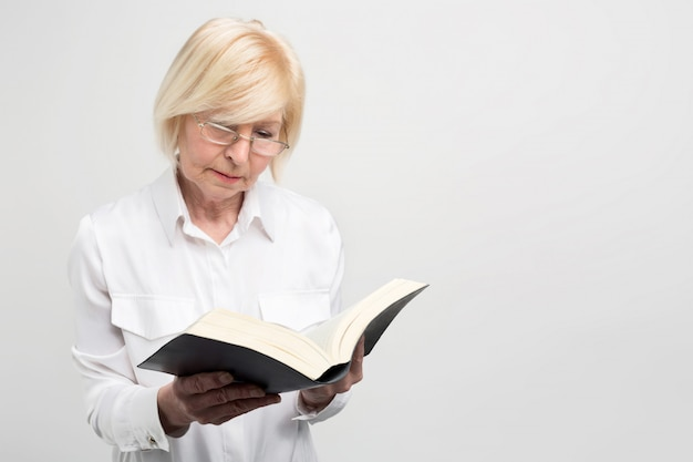 La donna senior di affari sta stando nella stanza e sta leggendo un libro. è molto interessante.