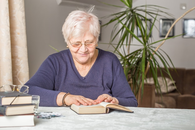 La donna senior legge concentrato in un libro nella biblioteca nella casa di riposo