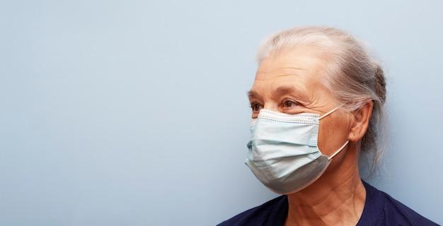La donna senior nella maschera medica non esamina la macchina fotografica su un fondo blu. bandiera