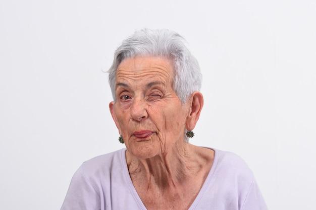 La donna senior sbatte l'occhio su fondo bianco
