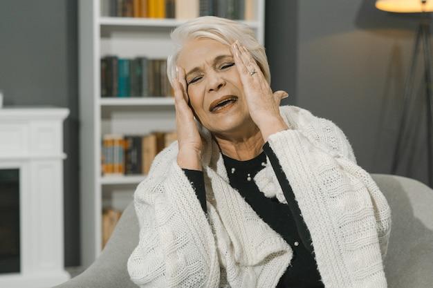 La donna senior sospira emotivamente toccando le tempie con le mani