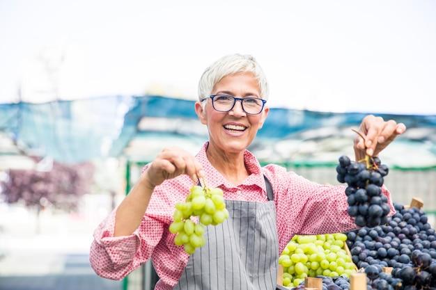 La donna senior vende l'uva sul mercato