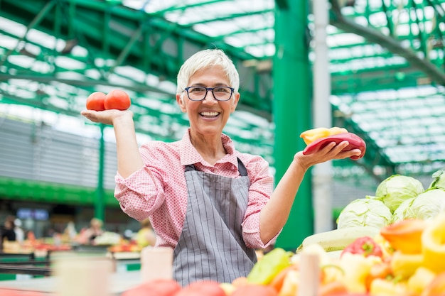 La donna senior vende la verdura sul mercato