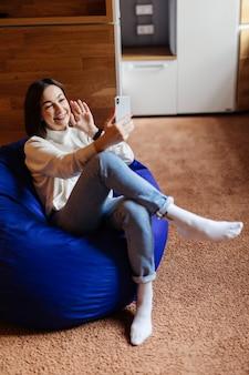 La donna sensuale in blue jeans e t-short bianca fa selfie con una videocall sul suo telefono