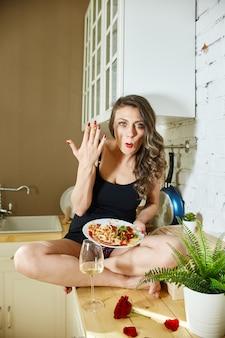 La donna senza complessi mangia la pizza e gli spaghetti a casa. gioia e risate sul volto della donna