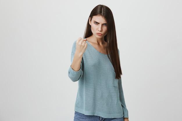 La donna seria arrabbiata minaccia o rimprovera qualcuno con il pugno