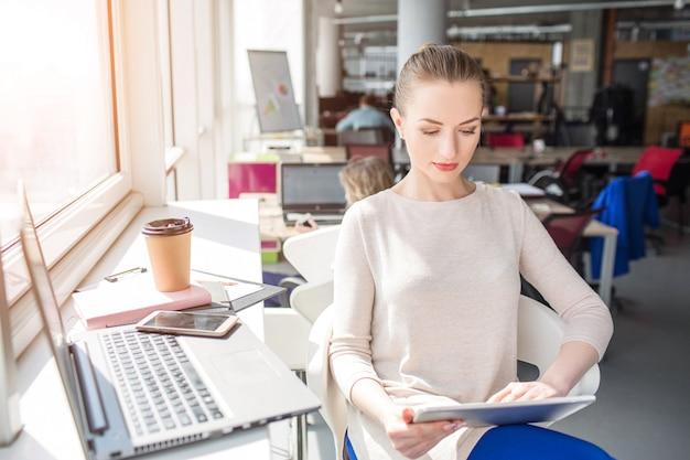 La donna seria di affari sta sedendosi al tavolo vicino alla finestra e sta guardando al tablet