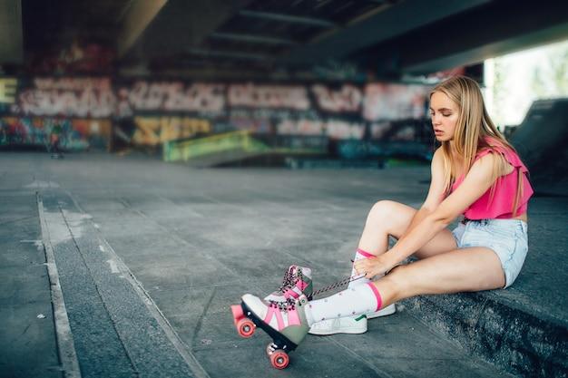 La donna seria è seduta e tira indietro i lunghi lacci sul rullo destro
