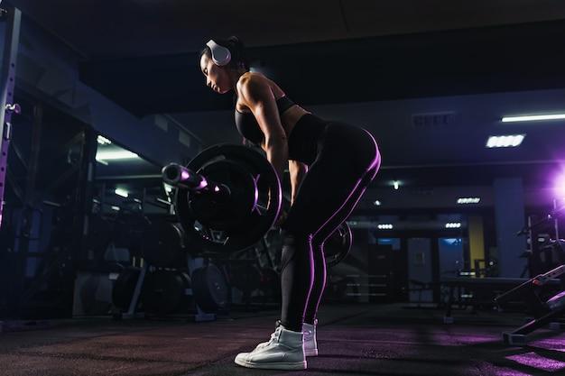La donna sexy in forma attraente in cuffie senza fili ascolta musica e si accovaccia con un bilanciere in palestra. allenamento della donna