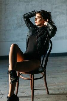 La donna sexy in giacca di pelle con le gambe nude posa sulla sedia in uno studio