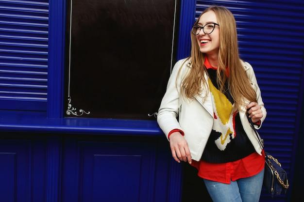 La donna si appoggia a una porta blu in piedi sulla strada