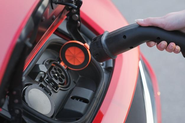 La donna si collega al caricabatterie nella presa della sua nuova auto elettrica rossa moderna. la donna sta tappando il veicolo elettrico per caricare la batteria dell'auto al parcheggio.