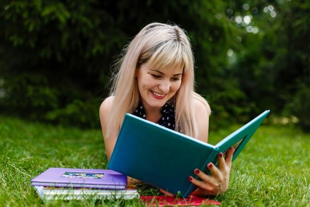 La donna si distende o si distende sul libro di lettura dell'erba verde in estate o primavera, vista superiore