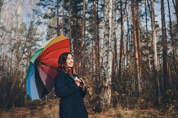 La donna si diverte con un ombrello colorato che cammina nei boschi. parco d'autunno. moda, accessori, passeggiate all'aperto