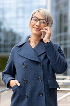 La donna si è vestita in vestito che parla sopra il telefono