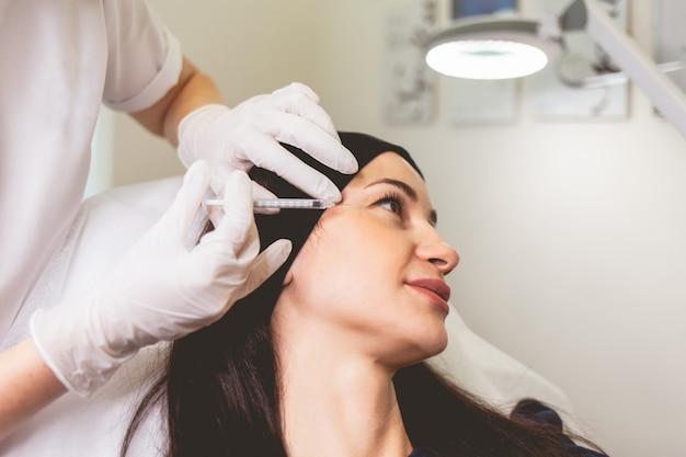 La donna si prende cura di se stessa e fa iniezioni ringiovanenti del viso