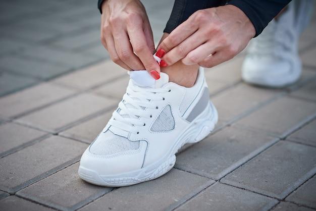 La donna si prepara per la corsa. mani femminili che lega i lacci delle scarpe su una sneaker sportiva