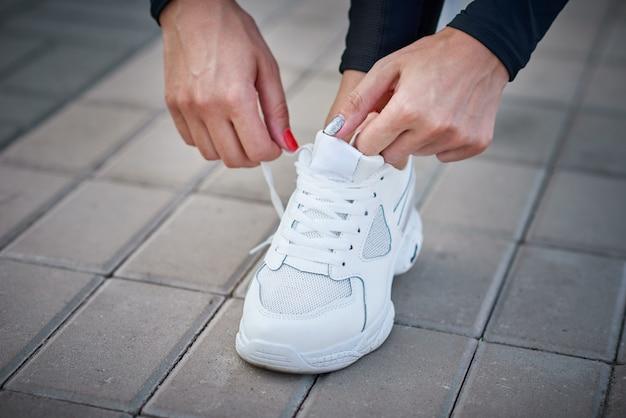 La donna si prepara per la corsa. mani femminili che legano i lacci delle scarpe su scarpe da ginnastica sportive