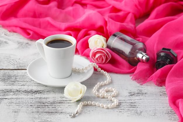 La donna si rilassa il tempo del caffè con la bottiglia dello scialle e del profumo sulla tavola