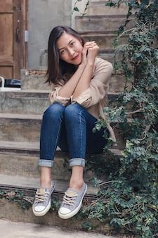 La donna si sedette sulla vecchia scala con piacere.