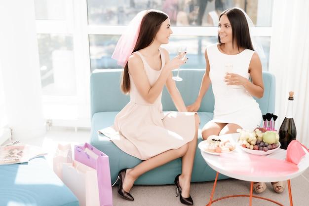 La donna si siede sul divano con un bicchiere di champagne.