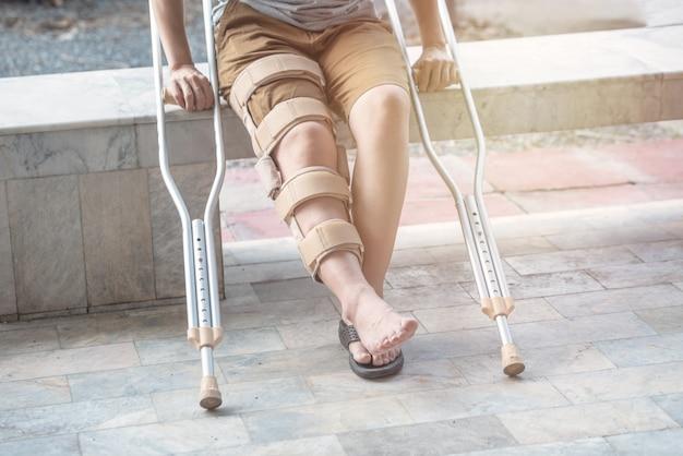 La donna si siede sulla panchina con bastone da passeggio e ginocchiera chirurgia di sostegno del ginocchio destro in tempo di recupero.