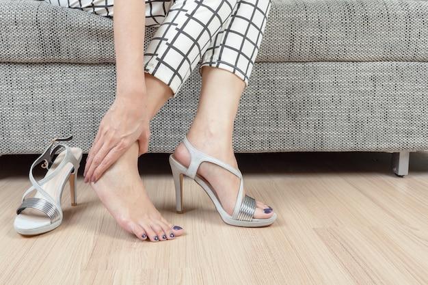 La donna si siede sulla sedia e la mano femminile con dolore al piede dopo, togli le scarpe