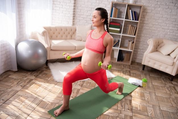 La donna si sta allenando con manubri a casa